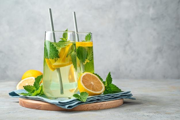 Освежающий лимонад с мятой на сером фоне. бодрящий летний напиток. вид сбоку, копия пространства.