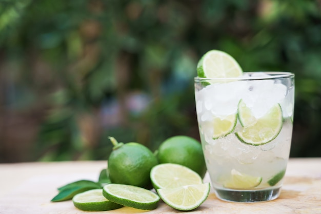 Refreshing lime soda with orange slice on wood