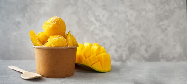 Refreshing mango ice cream in craft paper cup on gray background