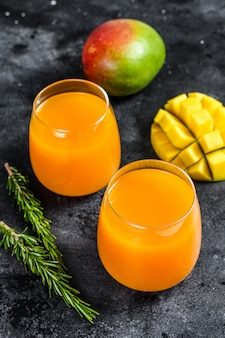Refreshing mango juice in a glass. black background. top view