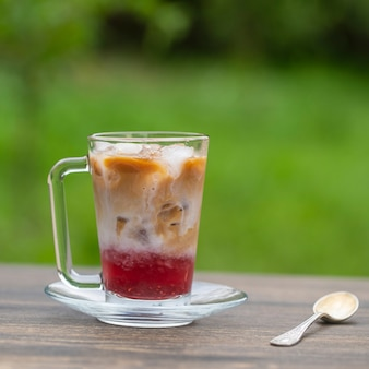 Refreshing milk iced coffee with raspberry syrup at the bottom on a summer day in the garden, close up