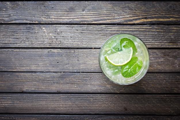 Освежающий мятный коктейль мохито с ромом и лаймом, холодный напиток или напиток со льдом на темной деревянной поверхности, вид сверху