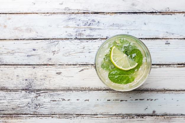 Освежающий мятный коктейль мохито с ромом и лаймом, холодный напиток или напиток со льдом на белой деревянной поверхности, вид сверху