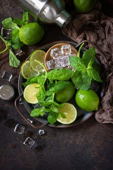 Refreshing mojito cocktail making. mint, lime, ice ingredients and bar utensils on a dark stone background copy space.