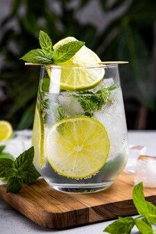 Освежающий мохито с мятой и льдом в стакане на летней зелени