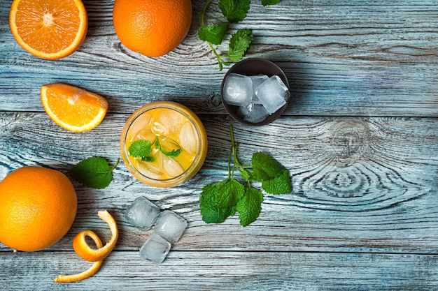 グレーブルーの机の上にミントと氷でさわやかなオレンジジュース。コピースペースのある上面図。 Premium写真