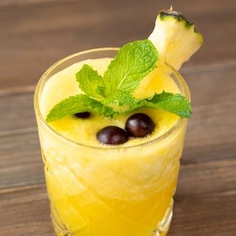 Refreshing pineapple summer drink on wooden table