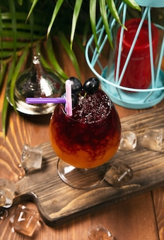 Refreshing red grape beverage in glass with ice cubes