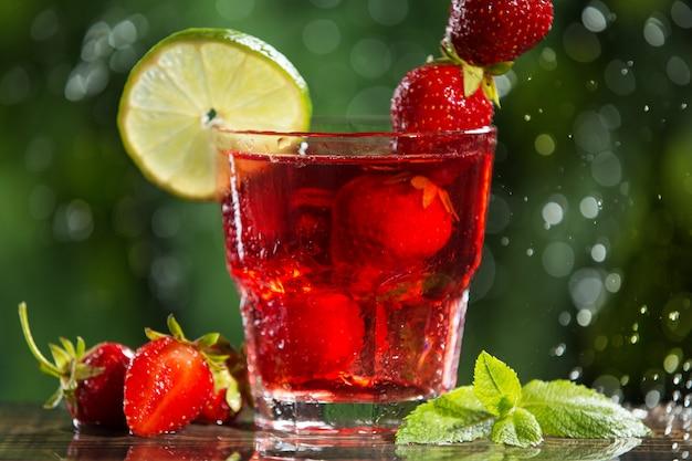 Освежающий красный клубничный напиток в бокале, с добавлением лайма, мяты и кубиков льда, рядом с ним клубника и листья мяты