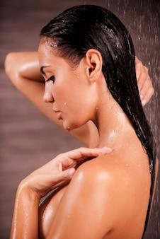 상쾌한 샤워. 샤워를 하는 아름 다운 젊은 벗은 여자의 측면 보기