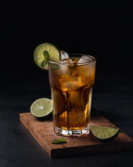 Refreshing soft drink with lime slices in glass cup over black
