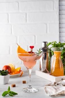 Refreshing summer alcoholic cocktail margarita on light wooden background