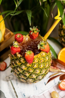 Refreshing summer alcoholic cocktail margarita with crushed ice and citrus fruits inside pineapple with strawberries on kitchen table