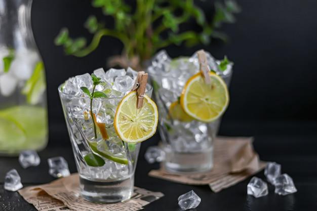 Освежающий летний алкогольный коктейль маргарита с колотым льдом, лаймом и мятой для украшения. водка всплеск. на темном деревянном фоне. на листьях газеты.