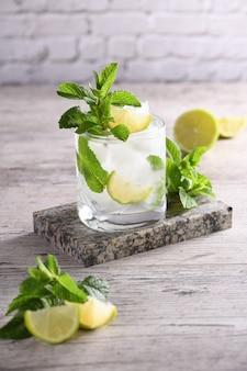 Освежающий летний алкогольный коктейль мохито со льдом, свежей мятой и лаймом