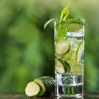 Освежающий летний газированный напиток в бокале, с добавлением лайма и ломтиков свежего огурца, на фоне зелени