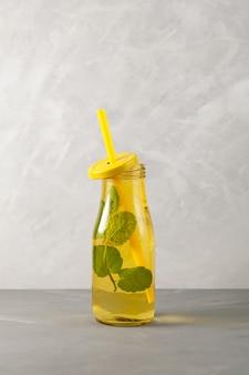 Освежающий летний напиток коктейль мохито с лимоном, лаймом и мятой в желтой стеклянной бутылке.