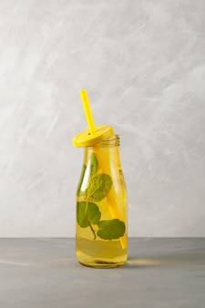 Refreshing summer drink mojito cocktail with lemon lime and mint in yellow glass bottle.