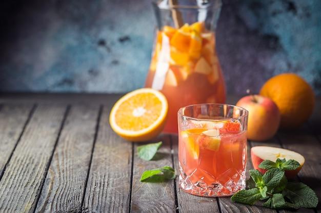 さわやかな夏の飲み物サングリアまたはグラスにフルーツを入れてパンチし、木製の上につまむ