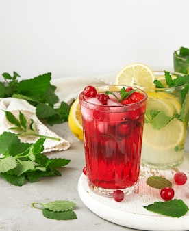 Refreshing summer drink of strawberries and cranberries on a white wooden board