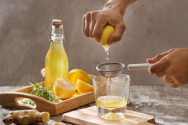 레몬, 생강, 로즈마리와 소박한 나무 테이블에 얼음으로 상쾌한 여름 음료, 복사 공간