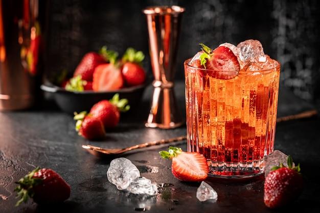暗い背景のグラスにイチゴと氷とさわやかな夏の飲み物
