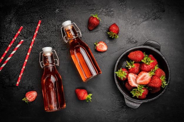 暗い背景の上面図にボトルに入ったイチゴとさわやかな夏の飲み物