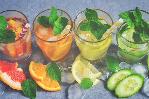 Refreshing summer drinks water with ice and lemon, orange, grape