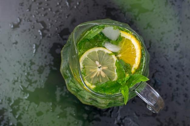 Refreshing summer lemonade in a transparent glass, mint, tarragon, lemon. toned