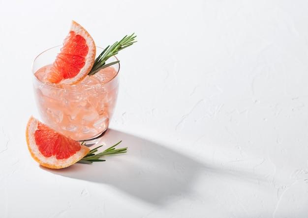 白い背景の上の氷とクリスタルガラスのさわやかな夏の赤いグレープフルーツカクテル