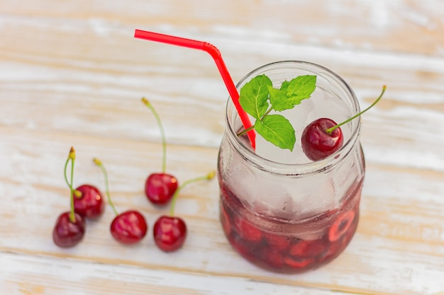 Refreshing summer sweet cherry cocktail with ice and mint on white wooden table