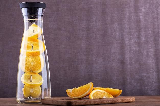 オレンジの爽やかな水。オレンジスライスを水に入れます。ガラスの瓶で飲む。自家製レモネード 。パーティーの飲み物。夏の飲み物。