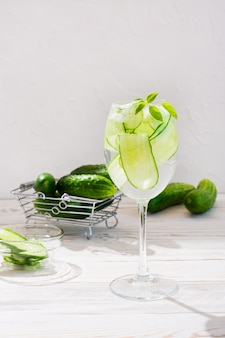 Refreshing water with slices of cucumber and basil leaves in a glass