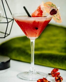 Refreshing watermelon cocktail in a glass with a piece of fruit and decorative umbrella.