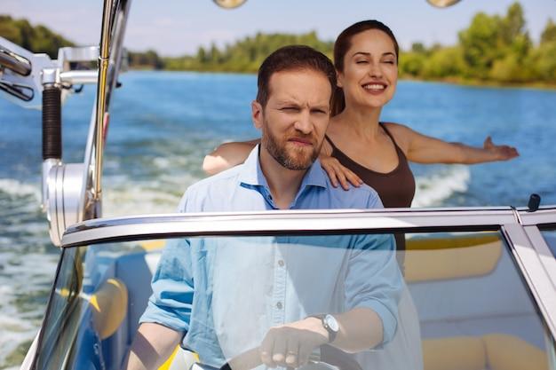 さわやかな風。夏のそよ風を楽しんで、彼女の夫がボートを航海している間笑顔の魅力的な若い女性