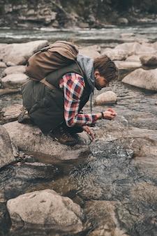 미지근한 물로 상쾌함. 산에서 하이킹하는 동안 강에서 물을 마시는 잘 생긴 젊은 현대 남자