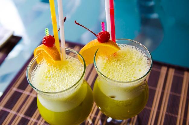 テーブルの上のレストランでオレンジとチェリーと氷でさわやかな黄色の飲み物