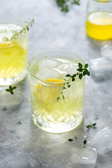 Refreshing yellow lemon glass of summer drink in glass. soda lemonade drink with herb.