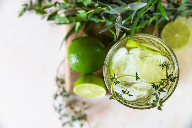 Освежающая вода с добавлением лайма и тимьяна. здоровый напиток и концепция детоксикации. летний напиток. выборочный фокус. вид сверху.