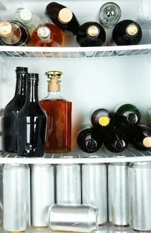 Холодильник полный бутылок с алкогольными напитками