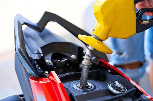 오토바이에 연료를 보급합니다. 가스 탱크에 삽입된 연료 노즐의 클로즈업