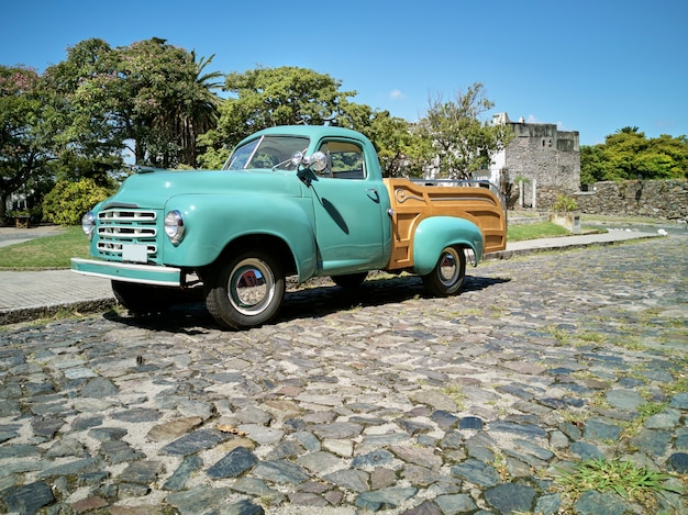 Refurbished old-timer pickup car on stone-flagged lane in historical colonia uruguay