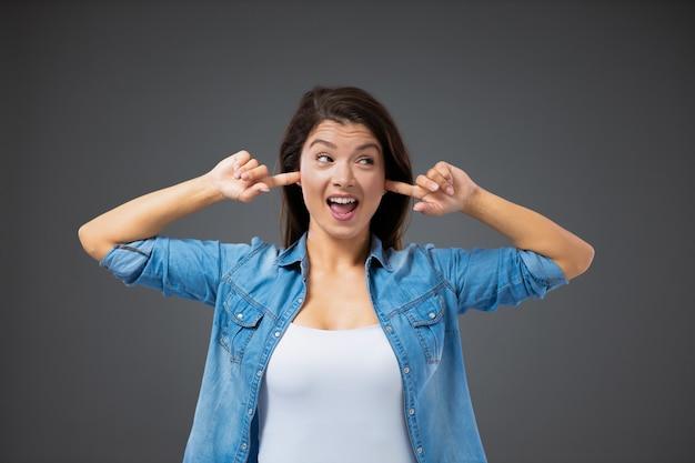 대화를 거부하고 문제를 피합니다. 평상복을 입은 어린 소녀가 손가락을 귀에 대고 눈을 피합니다. 귀찮게 하지마, 얘기할 때가 아니야