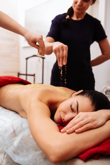 Восстанавливающие цели. концентрированные женщины поливают целебным порошком все тело расслабленной спокойной женщины