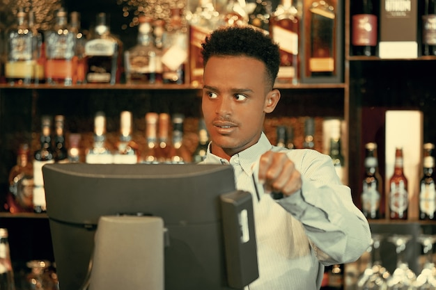 Registration male of bartender employee of a new order by a cash register.