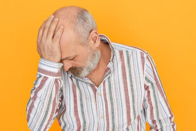 Сожаление, горе, стресс и депрессия. студийный снимок депрессивного несчастного лысого пожилого мужчины с густой бородой, держащего руку за голову, который чувствует стыд или сожаление о совершении большой ошибки, будучи раскаявшимся