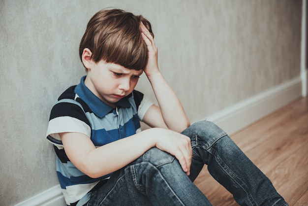 Regret sad little boy sitting alone loneliness,stressed depressed child crying having depression, anxiety, trouble of mental health, lonely kid boy with hand on head