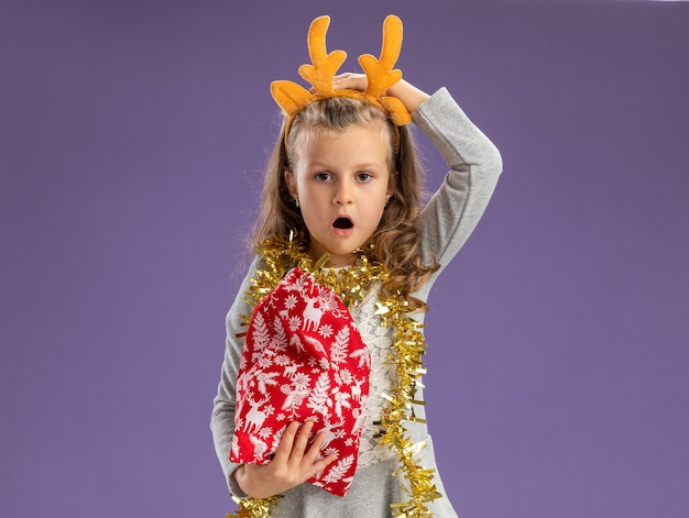 Regretted little girl wearing christmas hair hoop with garland on neck holding christmas bag putting hand on head isolated on blue wall