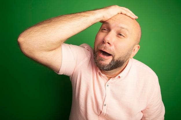 ピンクのtシャツを着て頭に手を置いている中年のハゲ男を見て後悔