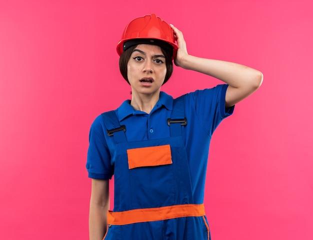 Deplorato guardando la telecamera giovane donna costruttore in uniforme mettendo la mano sulla testa